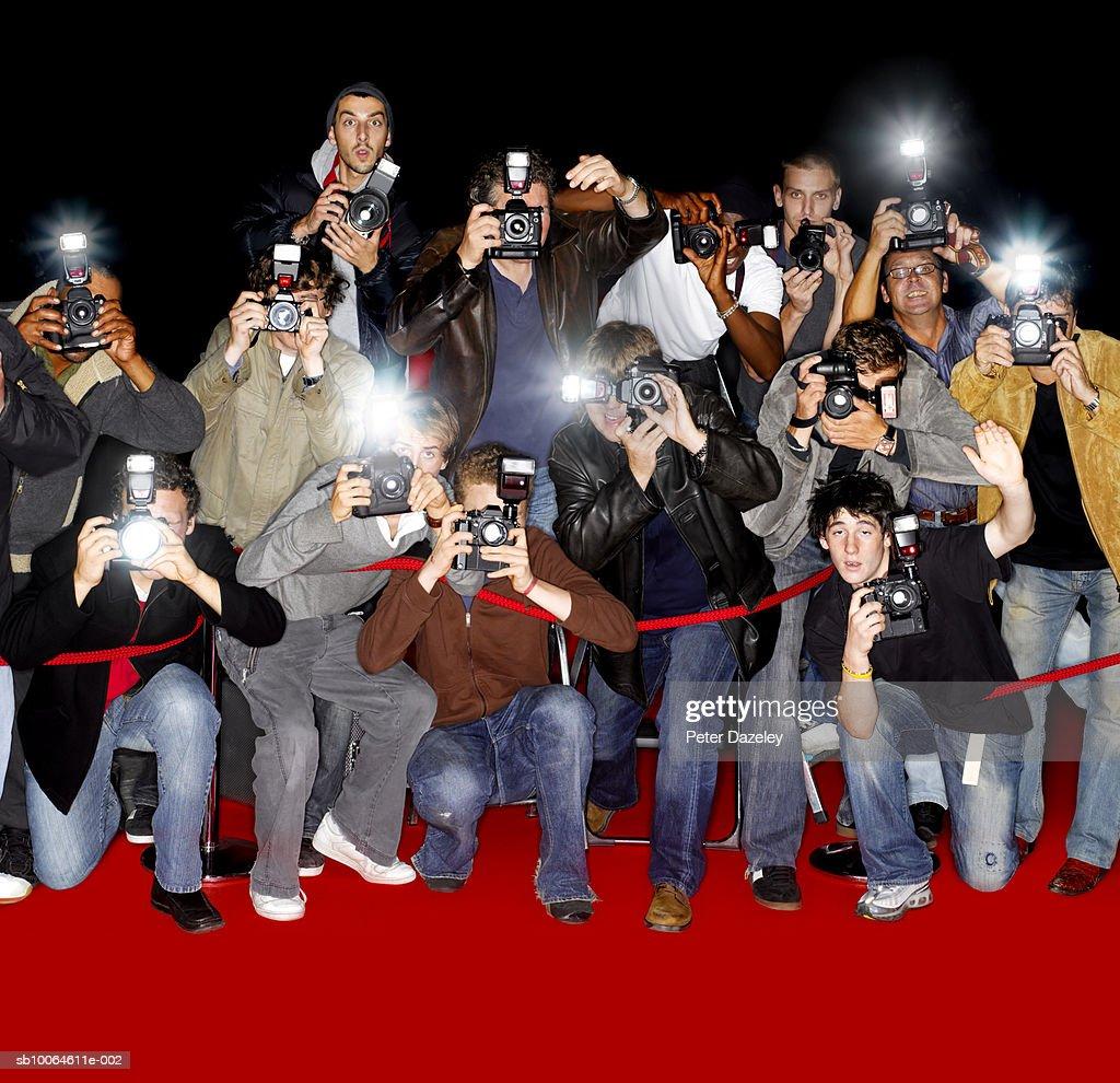Paparazzi behind cordon at premiere using flash cameras : Stock Photo