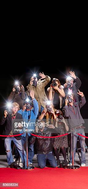 Paparazzi behind red rope barrier,