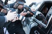 Paparazzi holding camera lens to car window