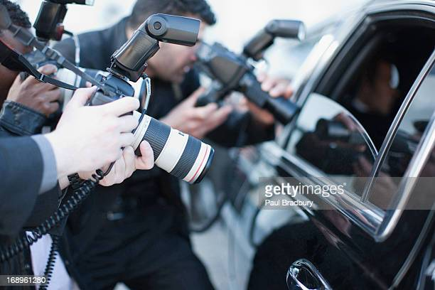 Paparazzi holding camera lens to car window