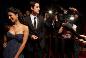 Paparazzi photographing celebrity couple in evening wear at event