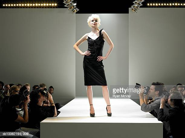 Paparazzi photographing fashion model on catwalk