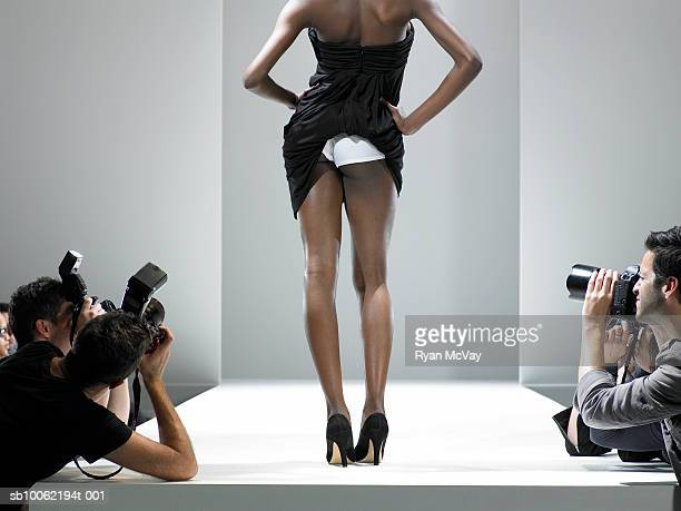 Paparazzi photographing fashion model showing underwear, on catwalk