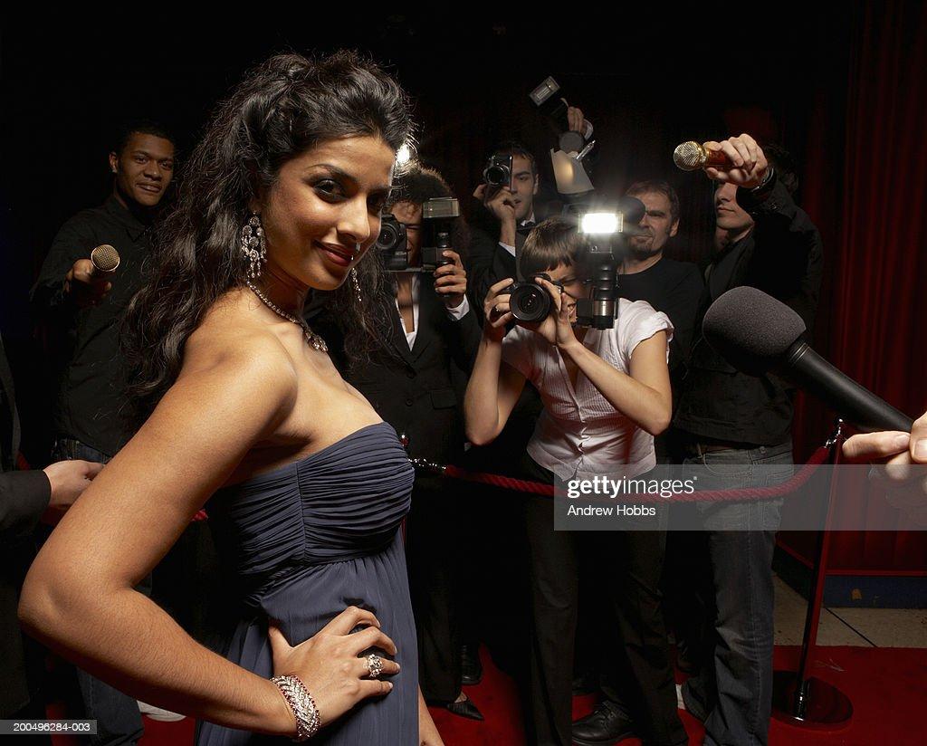 Paparazzi photographing female celebrity in evening dress, portrait : Stock Photo