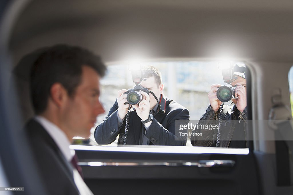 Paparazzi taking pictures of politician in car : Stock Photo
