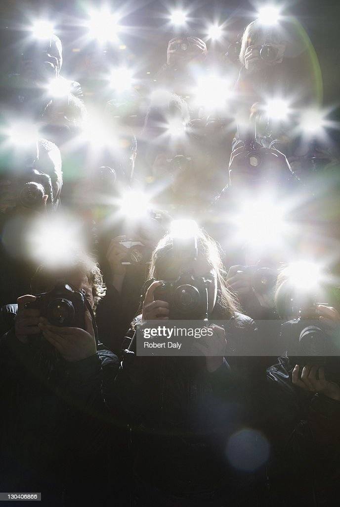 Paparazzi taking pictures with flash