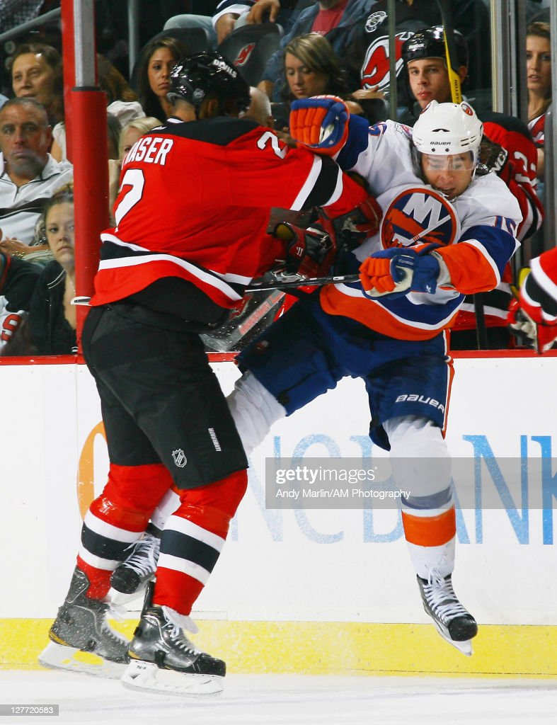 P.A.Parenteau #15 of the New York Islanders is checked by <a gi-track='captionPersonalityLinkClicked' href=/galleries/search?phrase=Mark+Fraser+-+Ice+Hockey+Player&family=editorial&specificpeople=5513661 ng-click='$event.stopPropagation()'>Mark Fraser</a> #2 of the New Jersey Devils during the pre-season game on September 30, 2011 at the Prudential Center in Newark, New Jersey.
