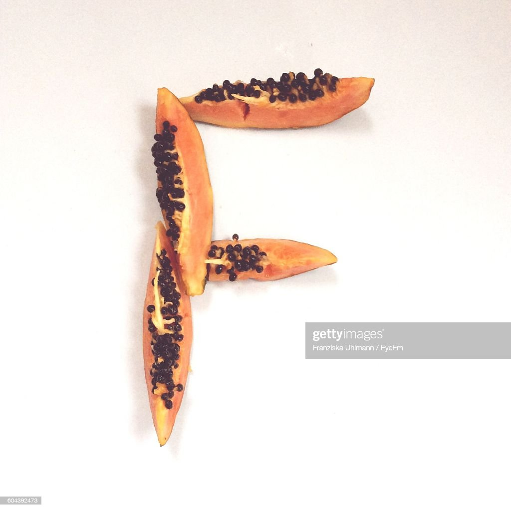 Papaya Slices Arranged In Shape Of Letter F Against White Background