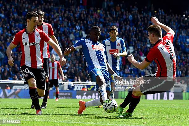 Pape Diop of RCD Espanyol competes for the ball with Aritz Aduriz and Aymeric Laporte of Athletic Club during the La Liga match between Real CD...