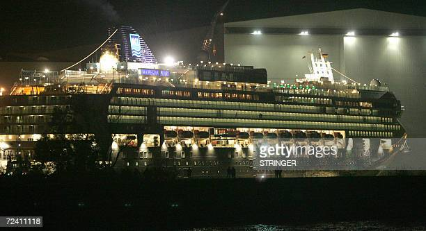 Residents watch as the cruise ship Norwegian Pearl sails through a narrow portion of the river Elms before entering the North Sea late 04 November...
