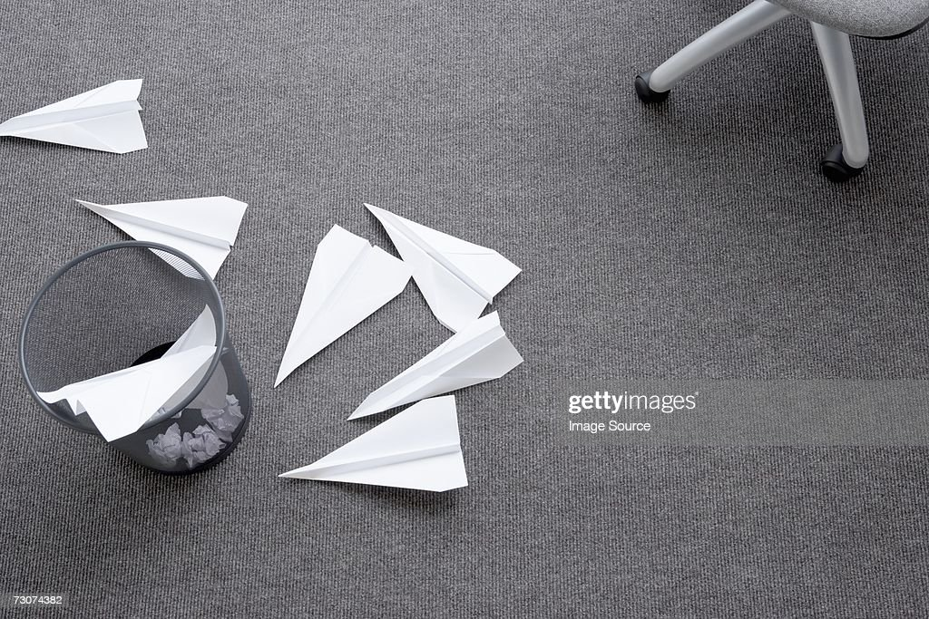 Paper aeroplanes a bin and a chair