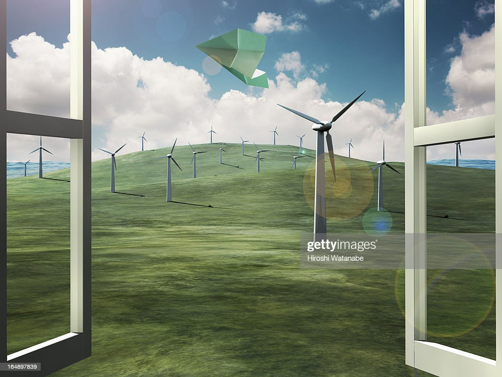 Paper airplane blowing for wind farm out of window : Stock Photo