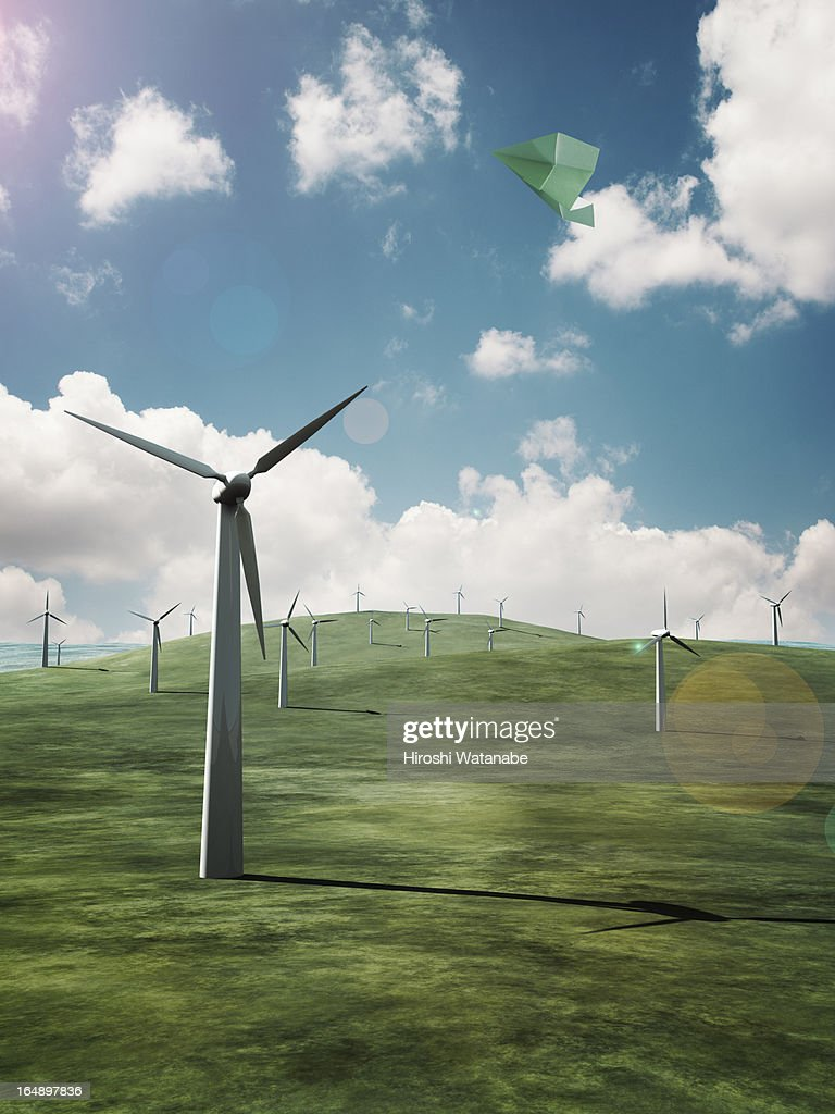 Paper airplane flying above the wind farms : Stock Photo