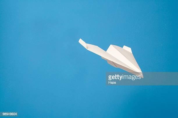 Paper airplane gliding through air