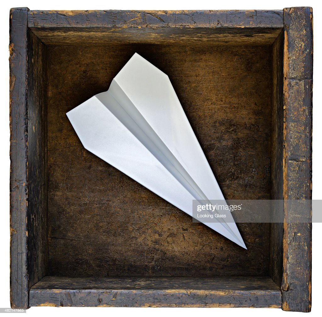 Paper airplane in wooden box