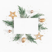 Christmas composition. Paper blank, christmas tree branches, golden decorations on white background. Flat lay, top view, copy space, square