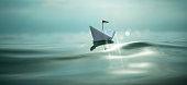 Papierschiff auf dem glitzernden Meer