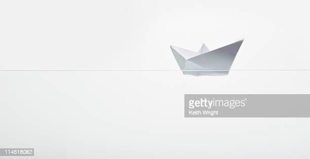 Paper boat floating along on white
