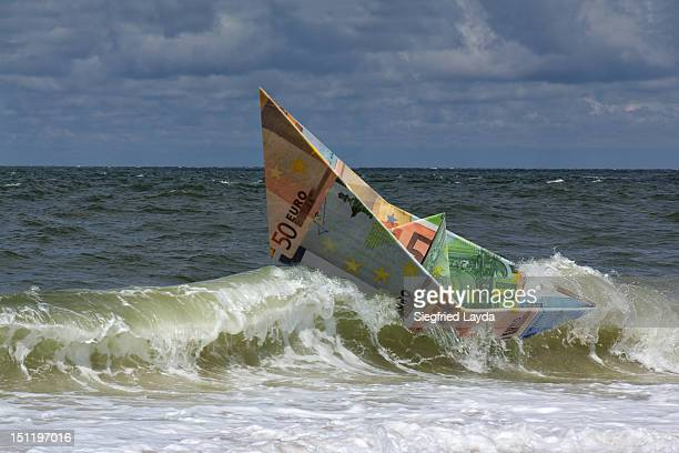 A paper boat made from euro banknotes in rough sea