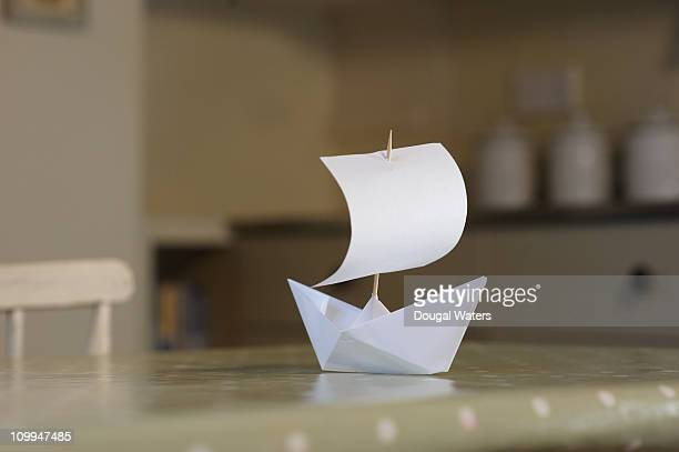 Paper boat on kitchen table
