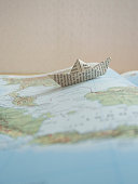 Paper Boat on map book photo no people
