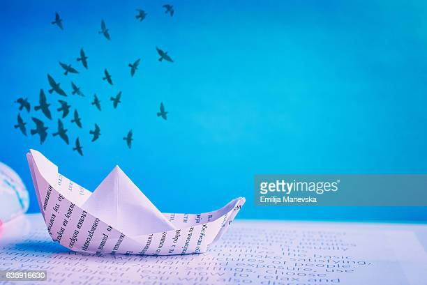 Paper boat sailing on open book
