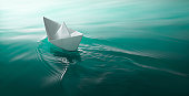 origami paper boat sailing on water causing waves and ripples