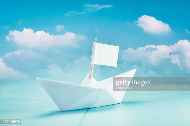 Paper boat with cloudy blue sky