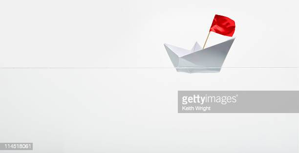 Paper boat with red flag
