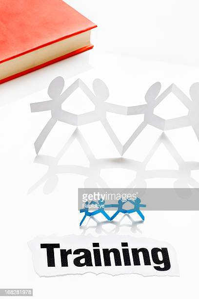 Ribambelle personnes à titre de la formation et livre sur blanc
