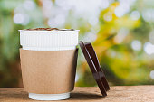Paper coffee cup or disposable cup on the wooden table on natural morning background with copy space for your text and logo.