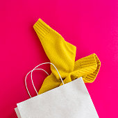 Paper craft package with purchases of women's clothing from which the yellow sleeve of the sweater sticks out. On a bright red background. Black friday concept. Top view, flat lay