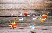 Colorful origami paper cranes on wooden background