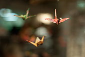 Colored paper folded into three oragami paper cranes hung from string as if flying.