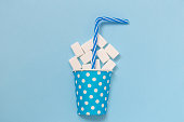 Flat lay of paper cup polka design full of sugar cubes and drinking straw against pastel blue background minimal creative concept.