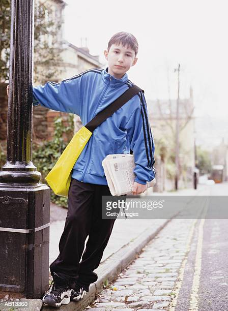 Paper delivery Boy (8-10) leaning from lamp post