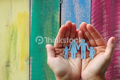 Paper family in hands on wooden coloured background welfare concept : Stock Photo