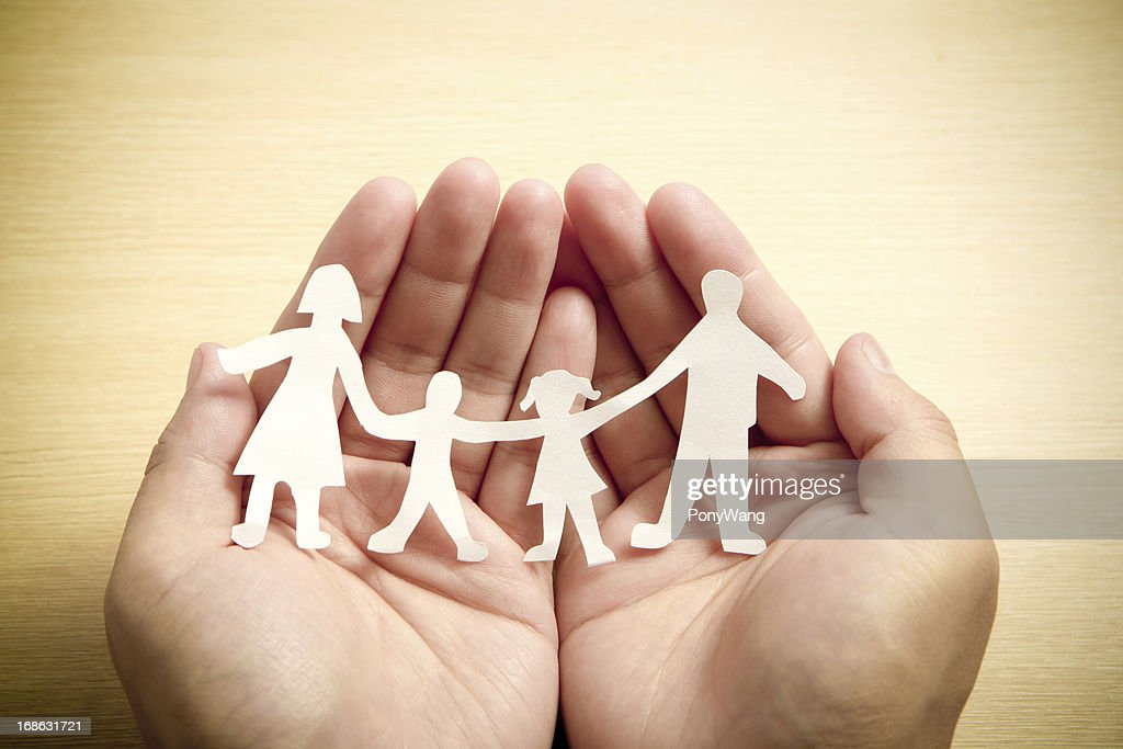 Paper family in hands with wooden texture background