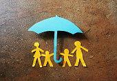 Paper family of four under a paper cutout umbrella