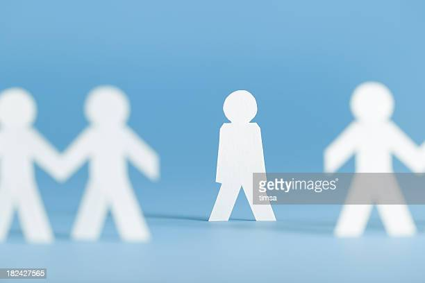 Paper figures holding hands with one alone not participating
