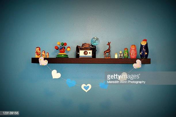 Paper hearts strung on shelf of collectibles