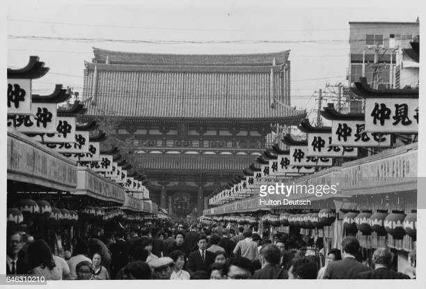 Paper lanterns and advertising signs line a busy shopping street leads to the temple