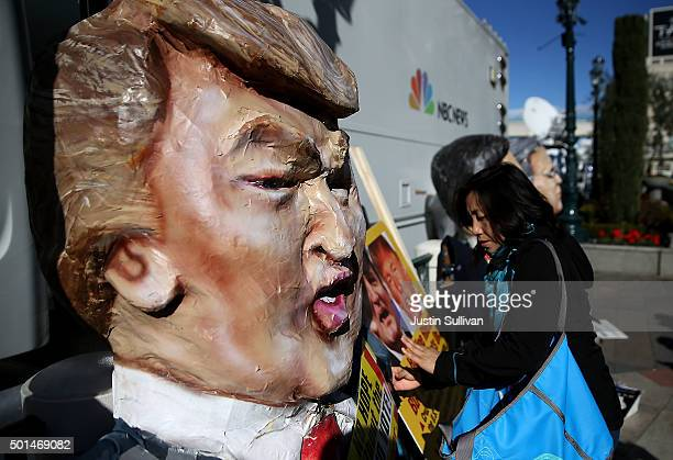 A paper mache likeness of republican presidential candidate Donald Trump sits on the sidewalk during a demonstration before the start of the CNN...