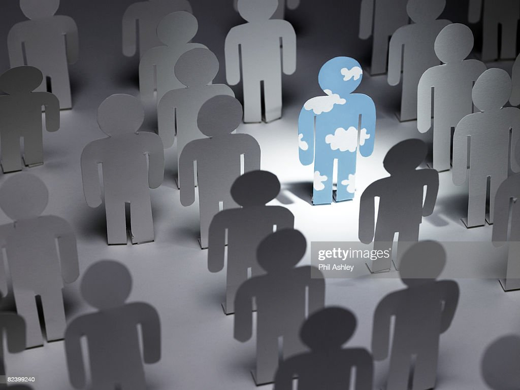 paper man with cloud pattern stands out of a crowd : Stock Photo