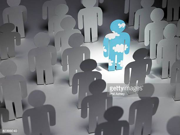 paper man with cloud pattern stands out of a crowd