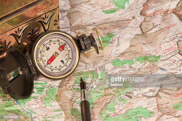 A paper map and a compass needed for planning a trip