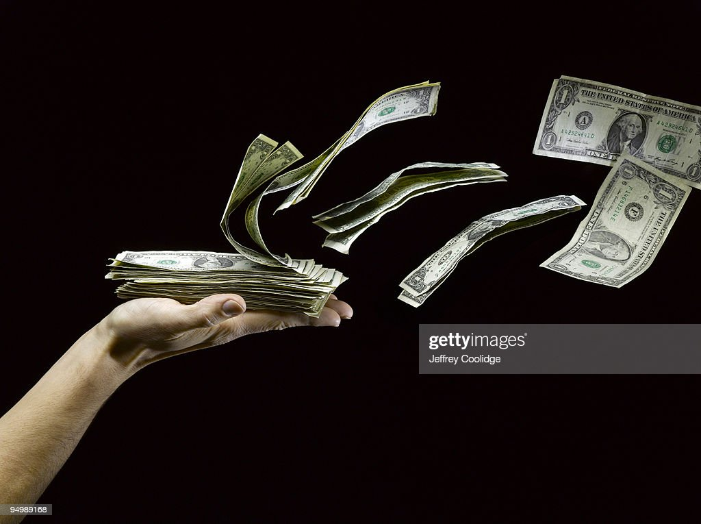 US Paper Money Flying out of Man's Hand : Stock Photo