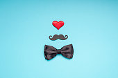 Creative flatlay overhead top view retro stylish black paper moustaches bow tie red heart turquoise background copy space. Men health awareness month fathers day masculinity concept blog social media