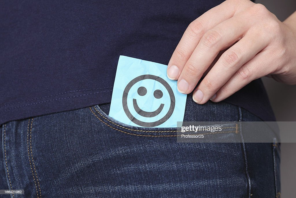 Paper note with smiling face in pocket of jeans