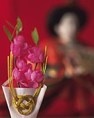 Paper peach flowers and Japanese female figurine, front view, differential focus